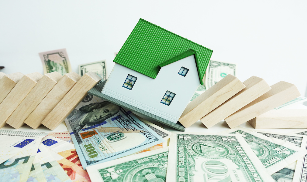 Housing market going to crash concept with miniature plastic house fall with domino pieces on cash banknotes