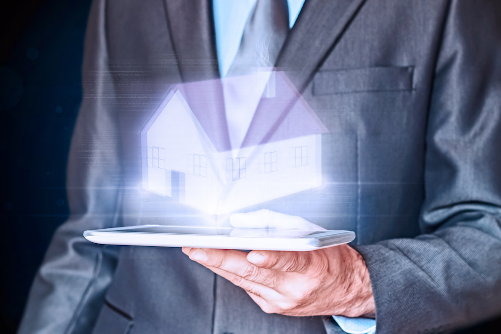 Businessman holding a virtual house. Virtual Holographic House. Business, mortgages and families concept