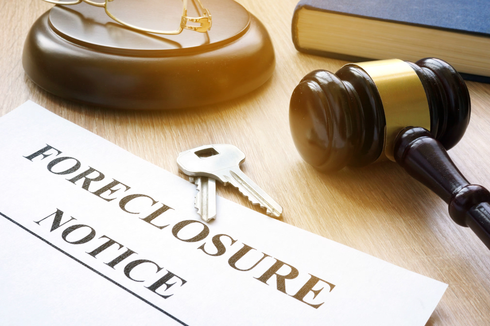 Foreclosure notice and keys on a court table.