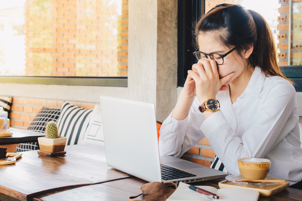 Asian businesswoman worry about her working on her laptop in office.