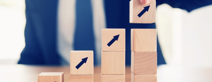 Business concept growth success process, Close up Businessman hand arranging wood cube with arrow stacking as step stair.
