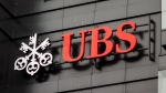 The logo of a Swiss bank UBS on a black wall of building