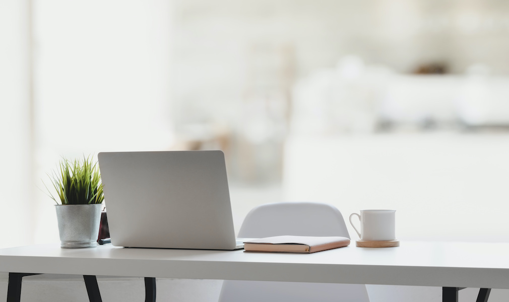 Comfortable workplace with laptop computer, coffee cup and office supplies