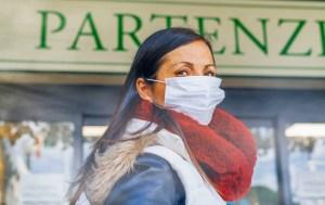 Coronavirus alarm in Italy, Europe. Woman at the airport entrance wearing respirator mask