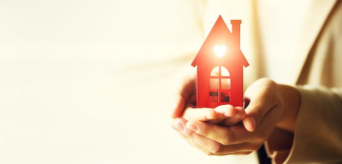 Female hand holding house key, real estate agent. Property insurance, security and cozy home concept. Copy space. Banner