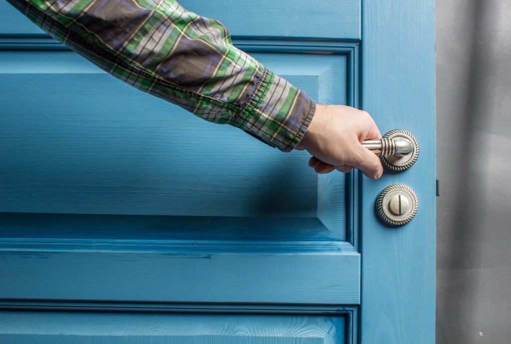 hand holding handle open door