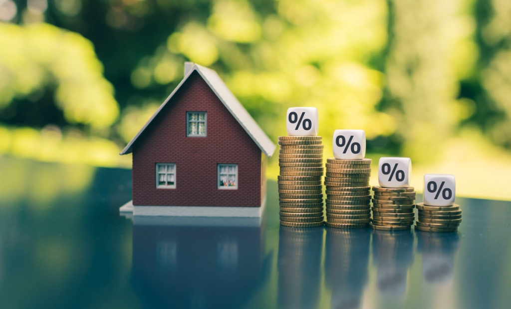 mortgage rates, Symbol for decreasing interest rates. Dice with percentage symbols on decreasing high stacks of coins next to a model house.