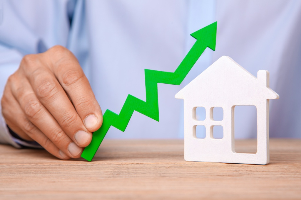 5006122 Rising house prices. Man is holding green arrow up in his hand and house