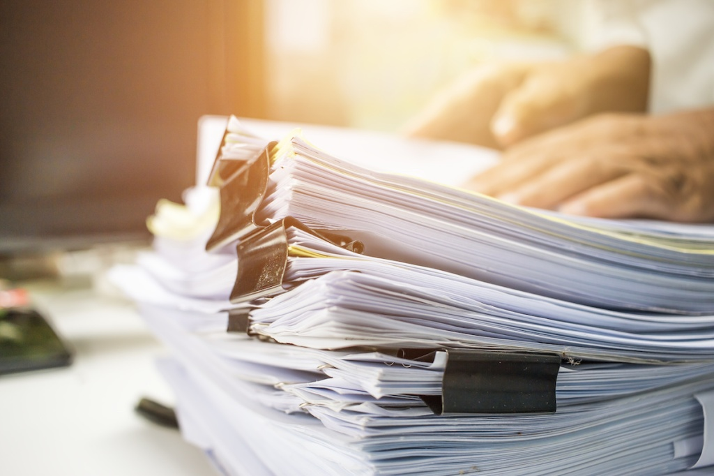 Businessman hands searching data information in Stack of papers files on work desk in office, business report paper or piles of unfinished documents achives with clips on offices indoor, Business concept