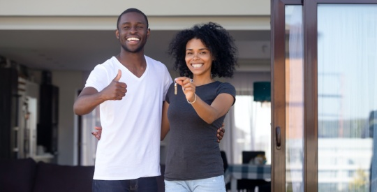 African couple standing on terrace hold keys of new house