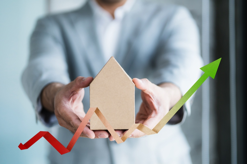 financial asset business concept with businessman hold house model with financial chart graph symbol