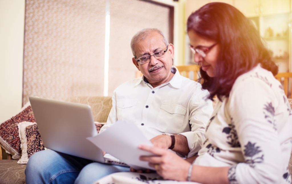 Senior Indian/asian couple accounting, doing home finance and checking bills with laptop, calculator and money while sitting on sofa/couch at home