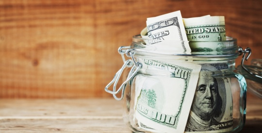 Dollar bills in glass jar on wooden background. Saving money concept.