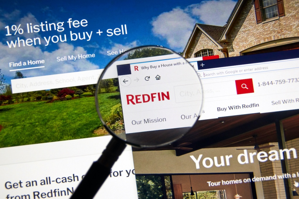 Redfin logo on official site under magnifying glass.