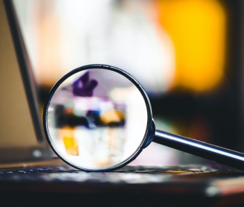 Magnifying glass on laptop keyboard. Internet security concept background.