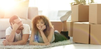 concept of moving to a new home. Happy couple lying on the floor