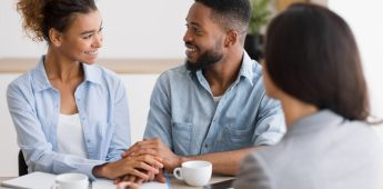 Smiling african american couple holding hands in financial advisor's office