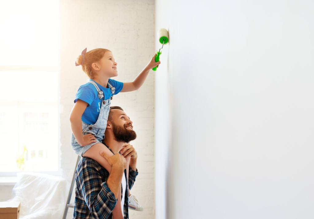 Repair in apartment. Happy family father and child daughter paints wall