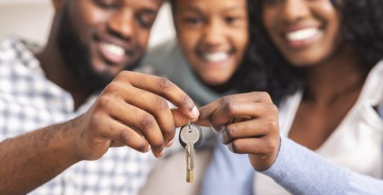 Happy african american family holding keys from their new home