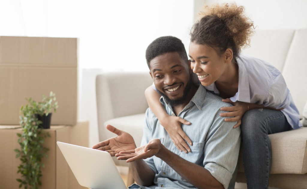 Husband Using Laptop Showing Something Wife Sitting On Couch Indoor